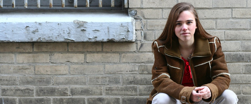 Young girl leaning against a wall
